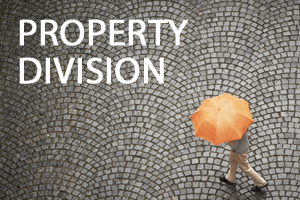 A person with an orange umbrella walking on a cobblestoned road with property division written beside him.